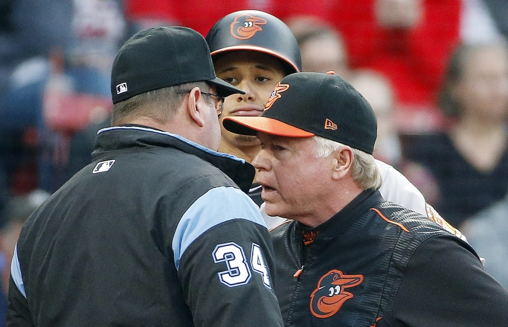 Baltimore Orioles manager Buck Showalter, right, talks with first base umpire Sam Holbrook as Manny Machado looks on during the first inning of a game Tuesday in Boston.