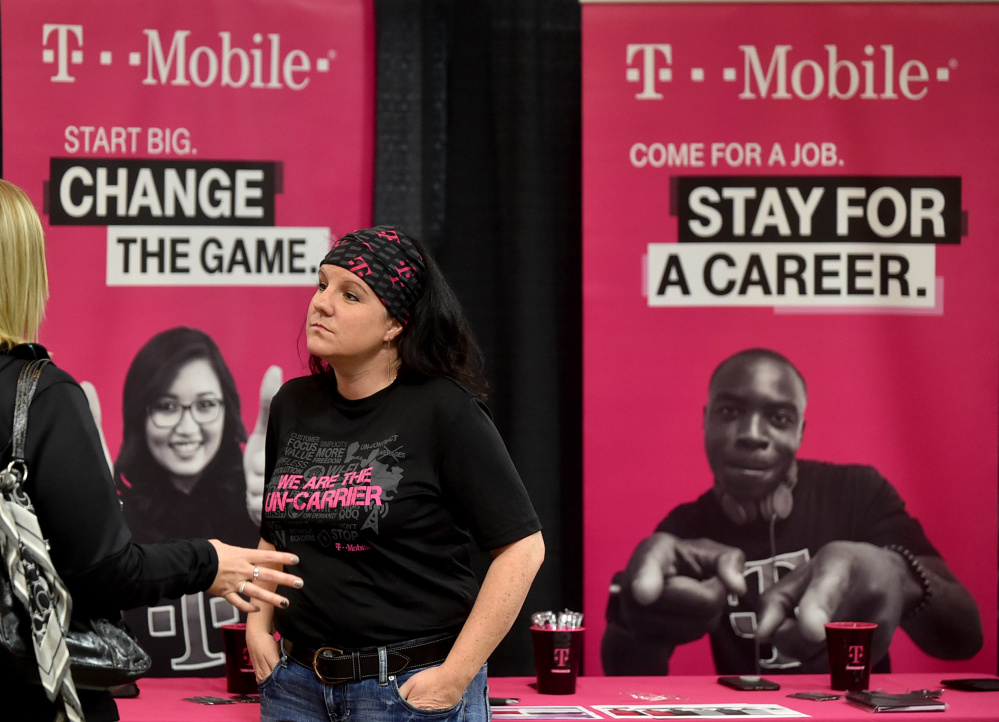 Tonya Clark, a recruiter from T-Mobile, speaks with a prospective employee Friday at the Growth Council job fair at the T&B Celebration Center in Waterville.