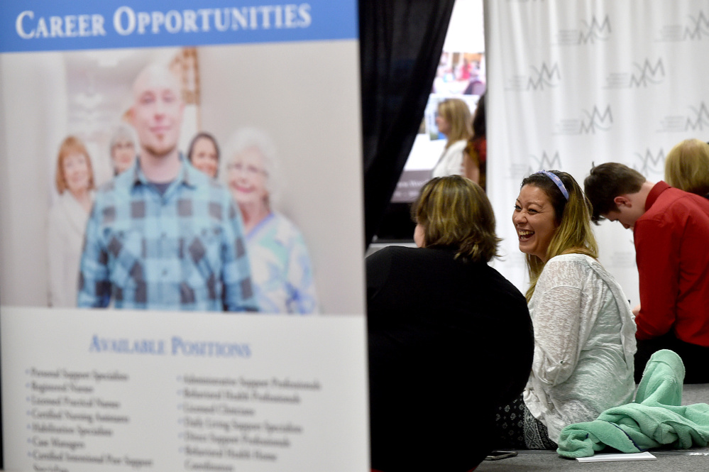 Jennifer-Lee Hesseltine, right, laughs as she talks with Kaitlin Taylor and they fill out job applications at the Growth Council job fair at the T&B Celebration Center in Waterville.