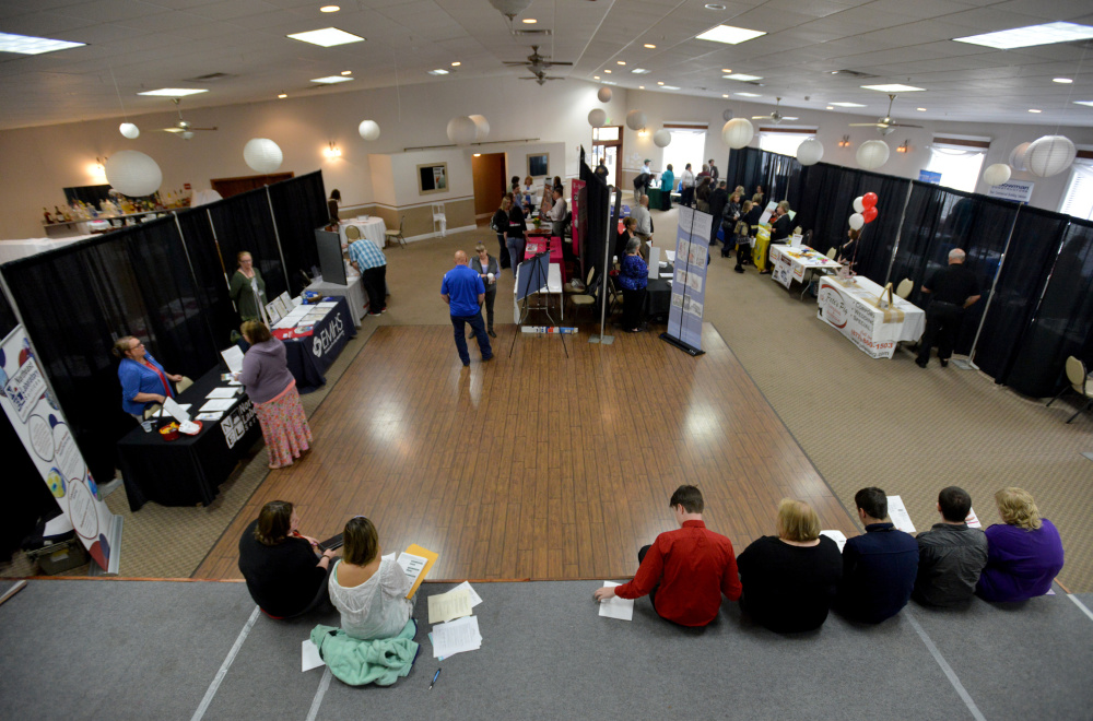 Job seekers sit on the stage filling out job applications Friday at the Growth Council job fair at the T&B Celebration Center in Waterville.