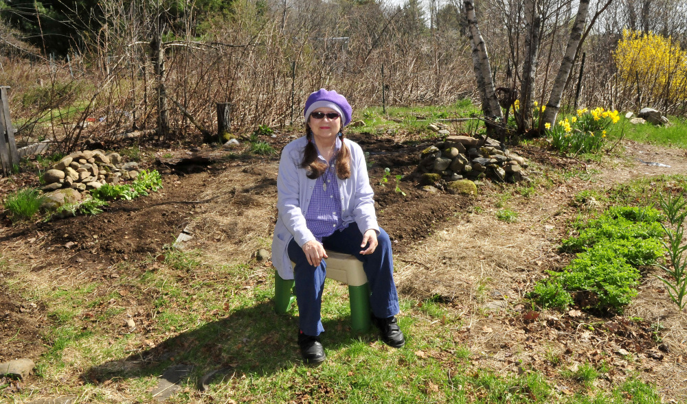 Author and mystic Annie Stillwater Gray finds solace in her vegetable and flower garden Thursday at her home in Solon.