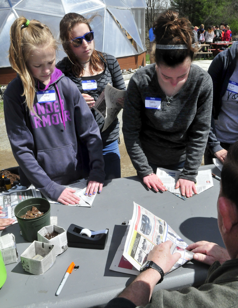 Skowhegan Middle School students Sumyr Taylor, left, Shelby Quirion and Nancy Giasson learn hold to fold newspaper into a biodegradable container to plant seedlings from instructor Gary Sinclair at one of the stations at the Marti Stevens Learning Center in Skowhegan during a forest field day on Wednesday.