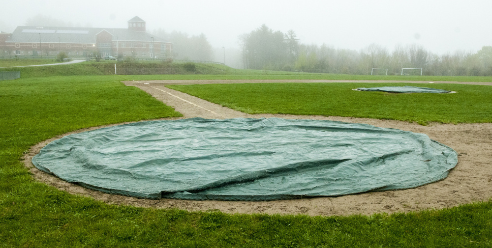 Tarps cover home plate and the pitcher's mound at Winthrop High School.