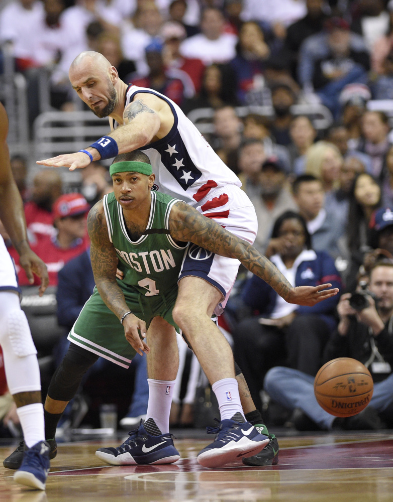 Boston Celtics guard Isaiah Thomas (4) passes the ball as Wizards center Marcin Gortat defends during Game 4 on Sunday night.