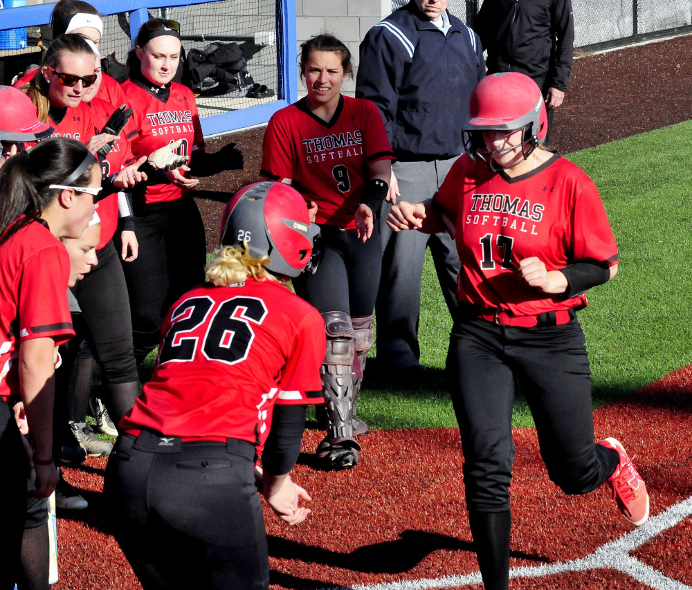 Thomas first baseman Korrie Laren touches home plate as teammates surround her after she hit a home run against Colby earlier this season in Waterville.