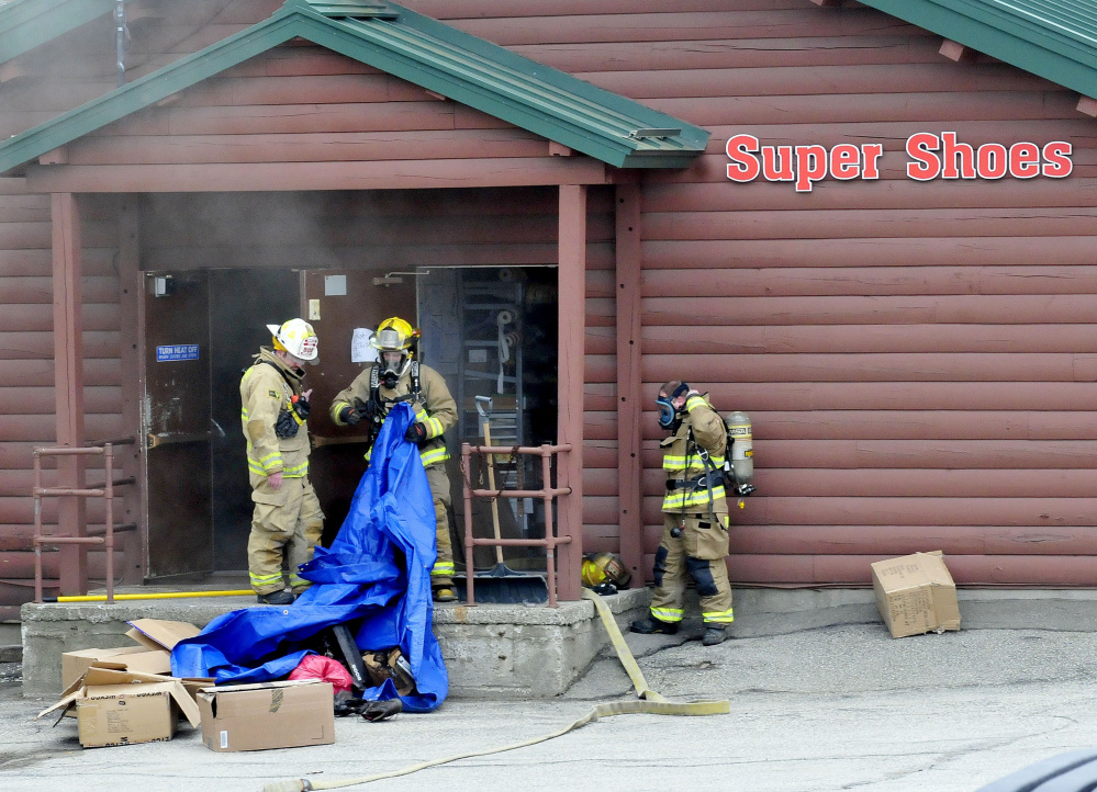 Waterville firefighters carry a tarp full of smoldering shoes and footwear out of the Super Shoes store in Waterville after a fire was reported on Tuesday.