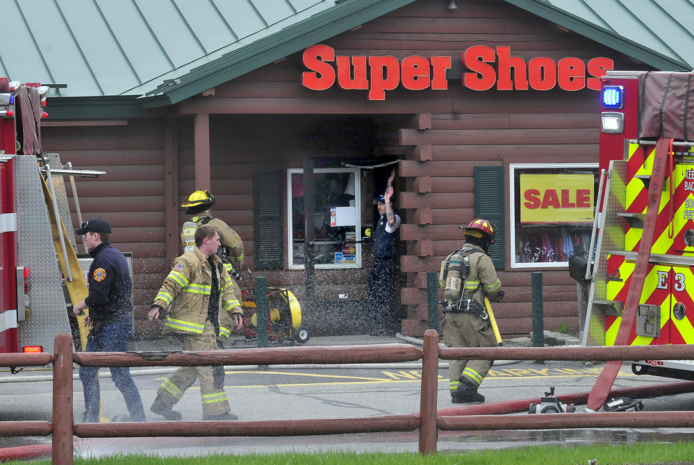 Waterville and Oakland firefighters responded to a report of a fire Tuesday at the Super Shoes store in Waterville. Smoke came out from a side entrance as firefighters carried out smoldering footwear.