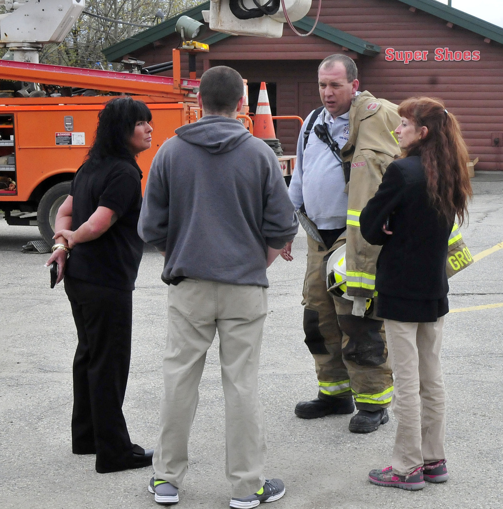 Waterville firefighter John Gromek speaks on Tuesday with Super Shoes store employees, from left, Nicole Witham, manager Wayne Ireland and Rebecca Leonard outside the Waterville store as firefighters extinguish a smoky fire there.