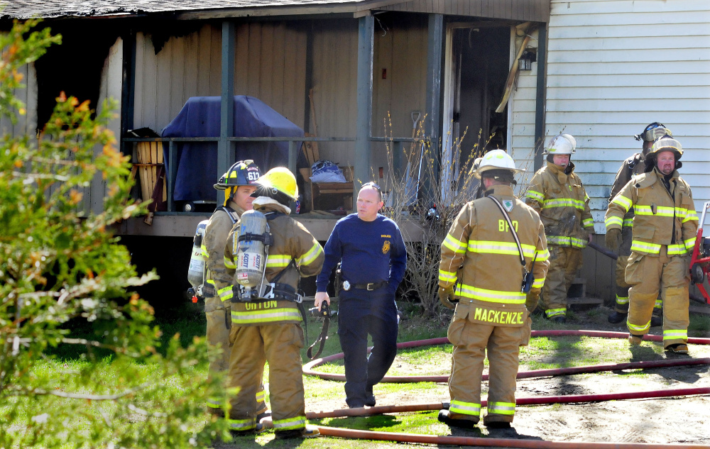 Jeremy Damren, center, of Office of State Fire Marshal, speaks with firefighters Wednesday while investigating a fire that destroyed a mobile home that morning on Smithfield Road in Belgrade.