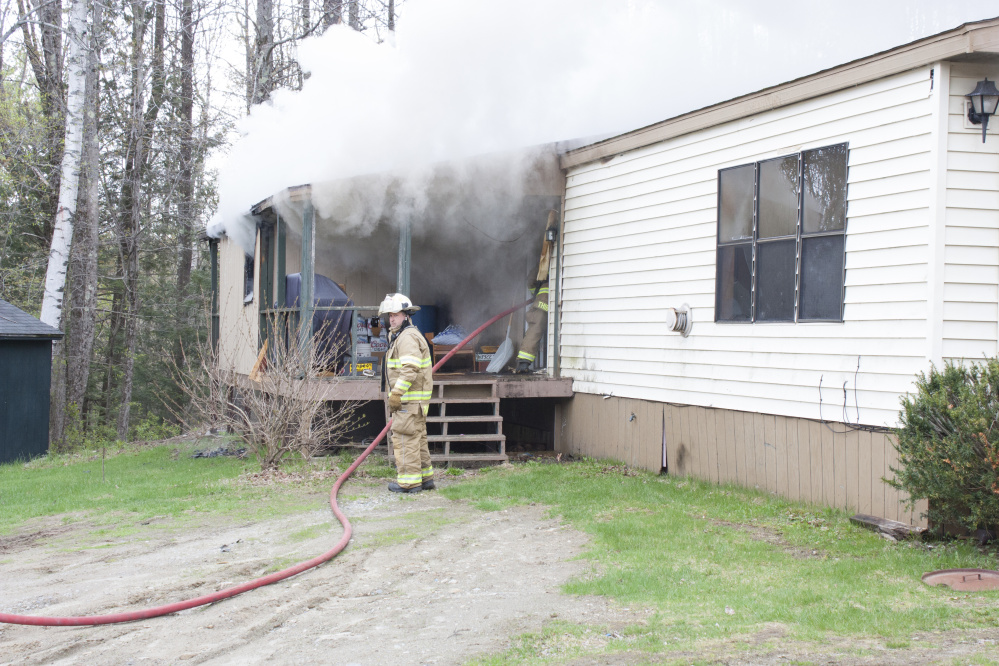 A firefighter works to put out a fire Wednesday morning at 905 Smithfield Road in Belgrade.