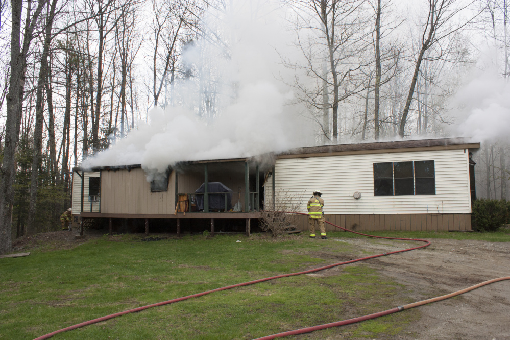 Smoke billows on Wednesday from the mobile home at 905 Smithfield Road in Belgrade.