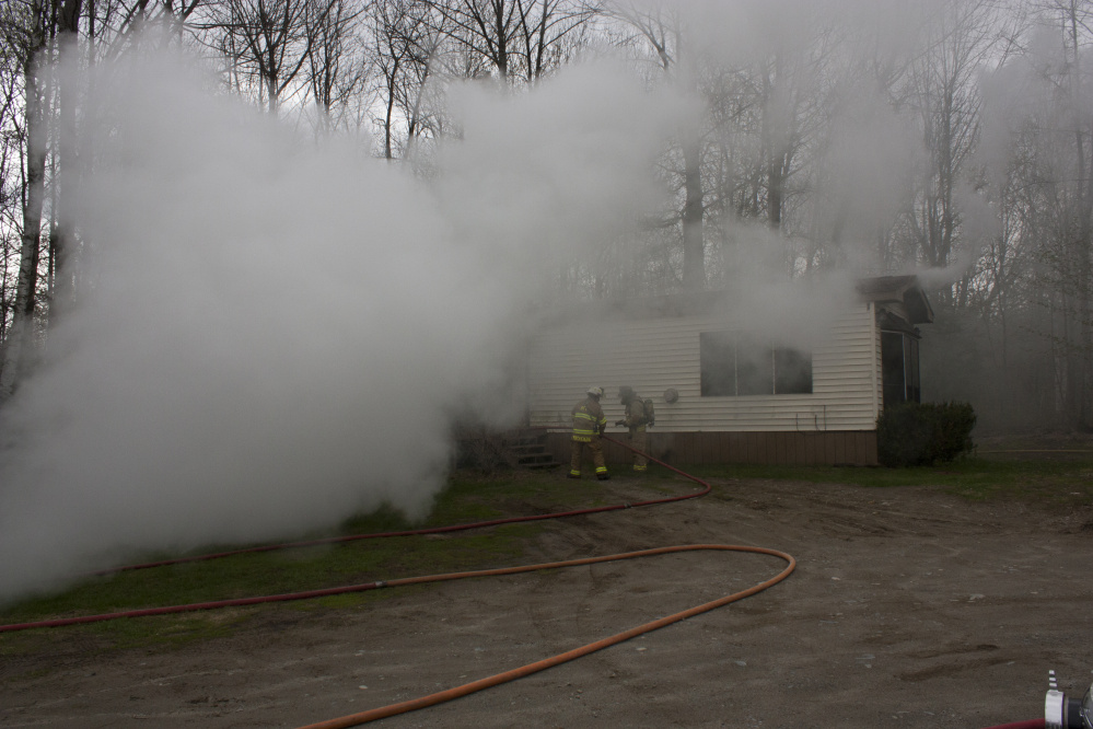 A mobile home at 905 Smithfield Road in Belgrade is barely visible Wednesday through the smoke.