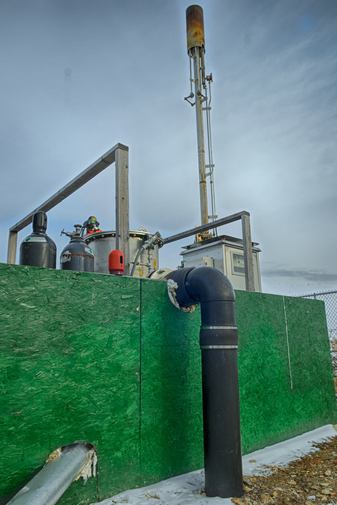 Staff file photo by Joe Phelan The black pipe carries methane from the landfill into the flare installation, where it is burned off in the stack above, as seen Jan. 10 at the Hatch Hill landfill in Augusta.