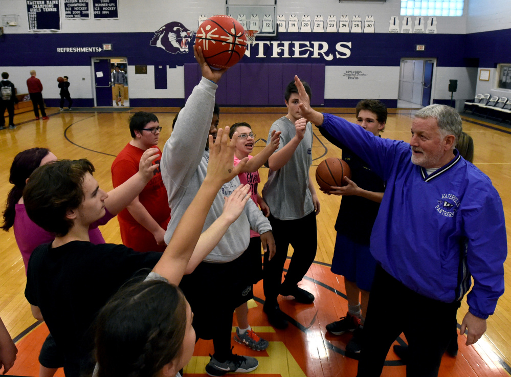 Waterville unified basketball coach Ken Lindlof, right, head calls his players into a circle for a pep talk before running drills during a practice last season.