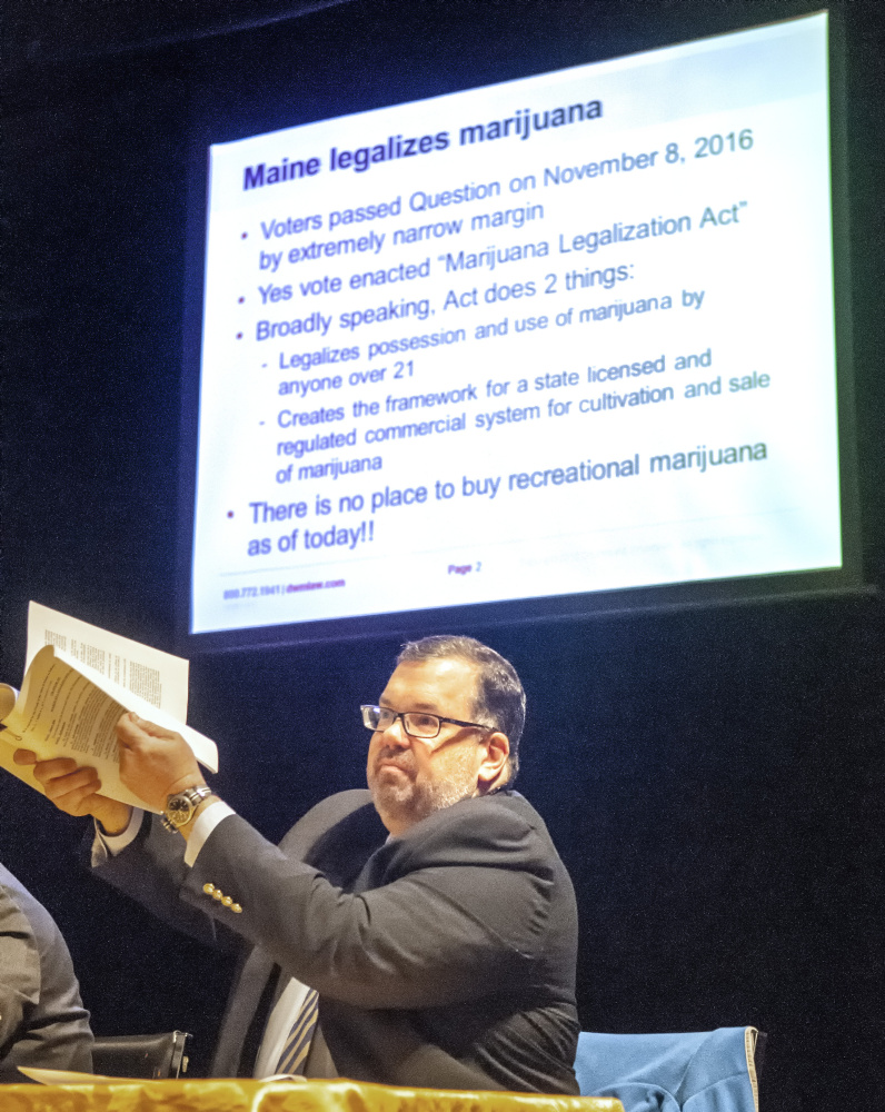 "Ted Kelleher, an attorney with Drummond Woodsum, holds up the 30 page Marijuana Legalization Act referendum, that passed last fall, on Friday during the ""Marijuana on Main Street"" event sponsored by Maine Downtown Center in Johnson Hall in Gardiner."