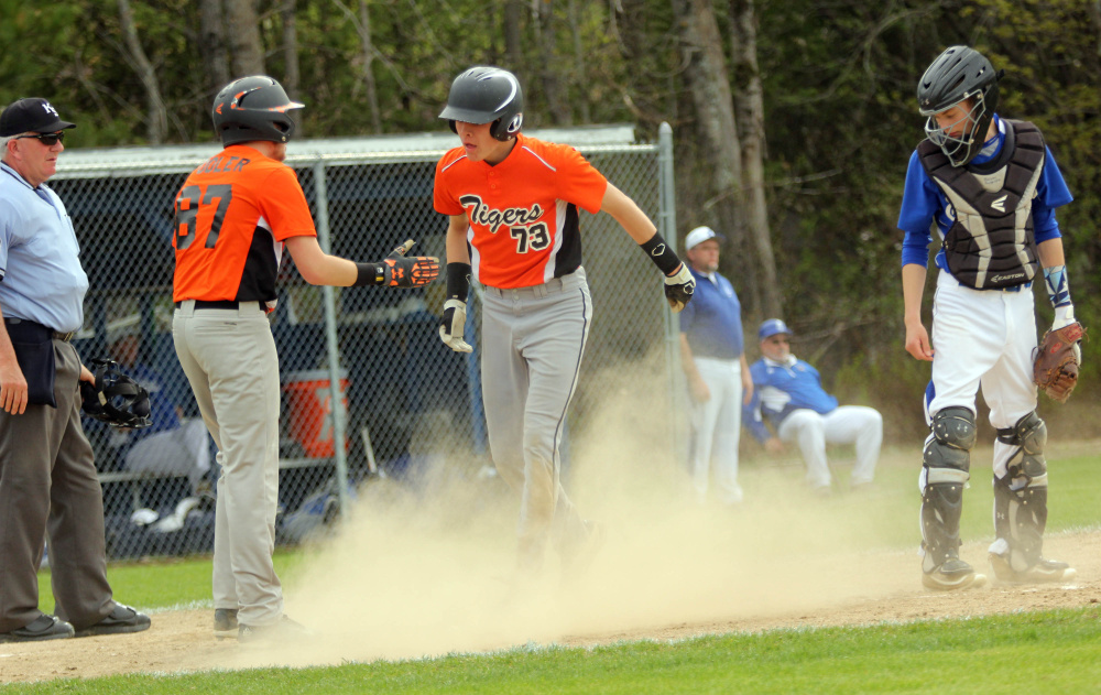 Photo by Jeff Pouland   Gardiner Area High School's Alic Shorey gets congratulated by Nick Pooler, left, after scoring a run during Saturday's game against Erskine Academy in South China.