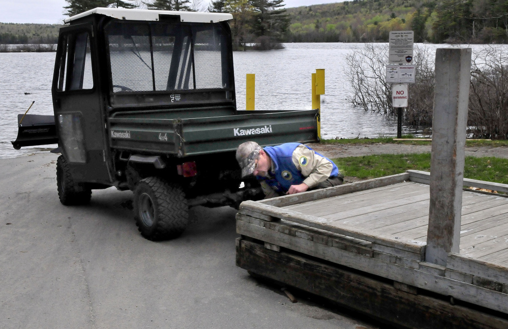 Derek Ellis, Lake George Regional Park resource manager, uses the new all terrain vehicle on Thursday to line up a dock that will be moved into the lake at the boat launch on the Canaan side of the park. The work vehicle was donated by the Somerset County Sheriff's Office.