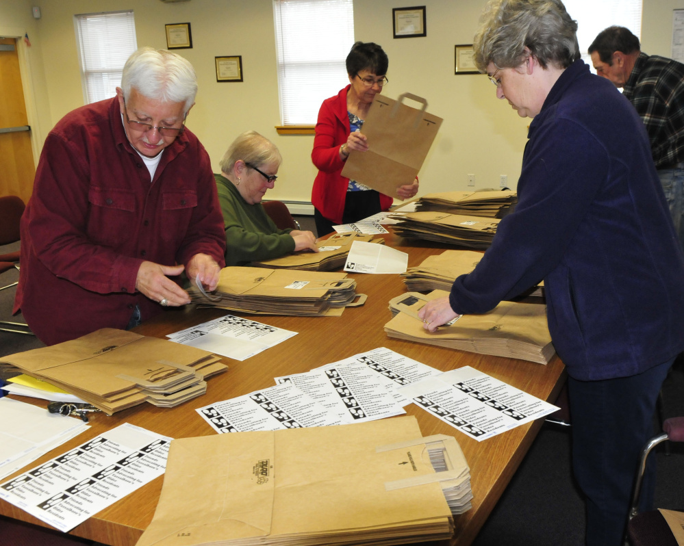 On Monday members of Vassalboro's FAVOR committee, Friends Advocating for Vassalboro's Older Residents, including Jim Schad and Town Manager Mary Sabins, put stickers on bags for the Services for Seniors fair at the town office on May 25.