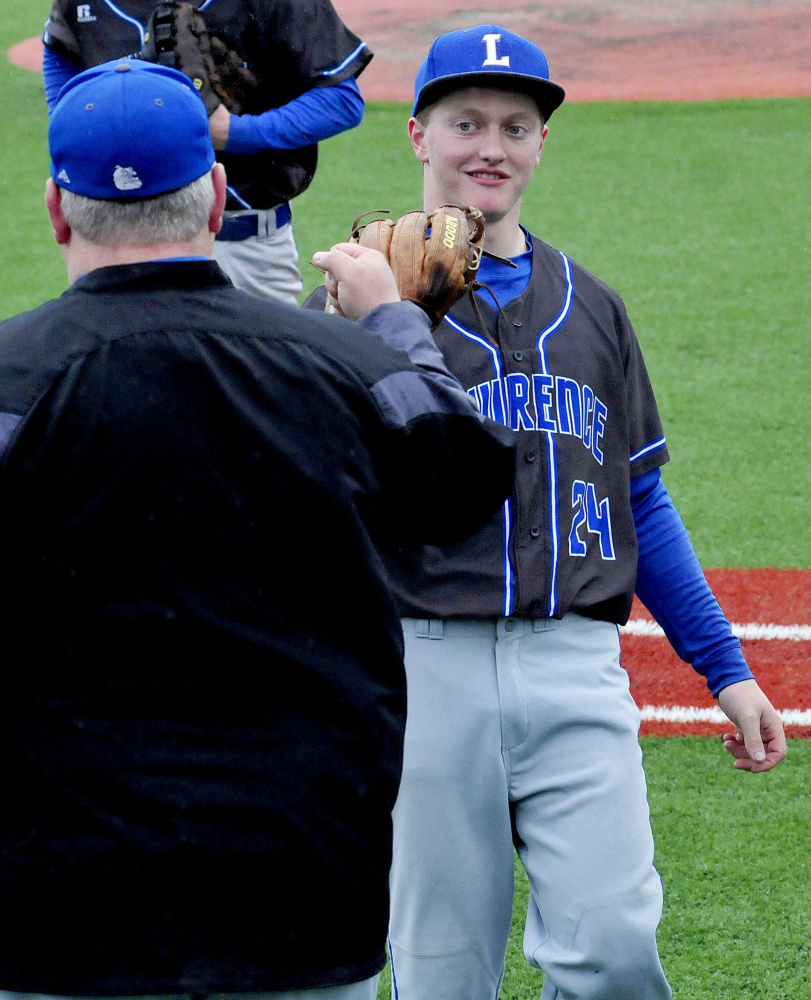 Lawrence baseball coach Rusty Mercier congratulates pitcher Riley Parlin after a good inning against Messalonskee on Monday.