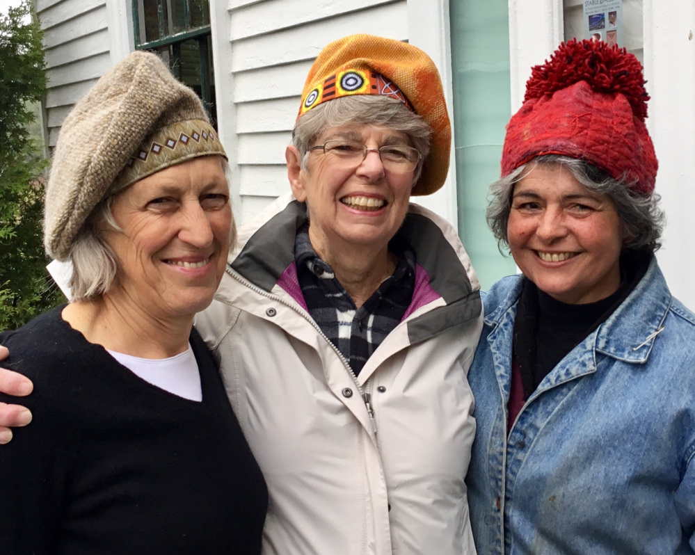 "Stable Gallery artists, from left, Polly Smith, Mary Hall and Roz Welsh model hats created by Susan Perrine""."