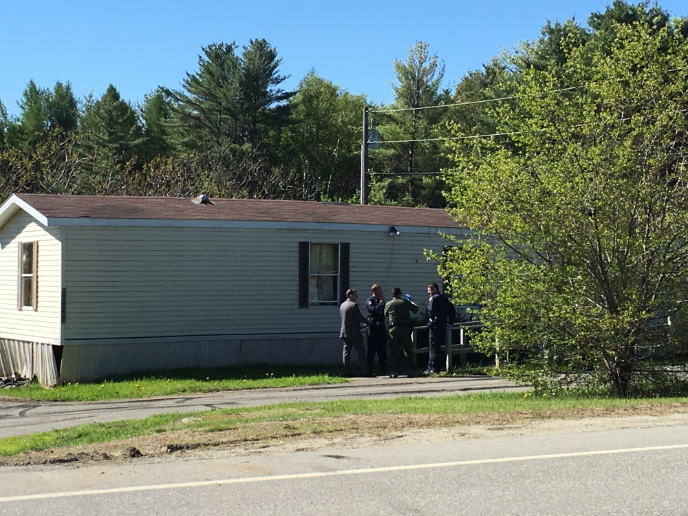 Authorities gather Saturday morning outside the Belgrade home where one person was killed and one was injured in an officer-involved shooting the previous night.