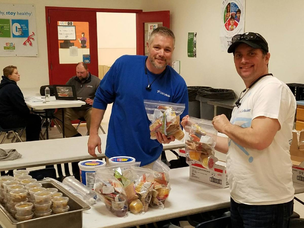 U.S. Cellular associates Kirk Fongemie, left, and Gaylon Wilkens recently helped the Boys & Girls Club of Greater Waterville on its Weekend Backpack Initiative.