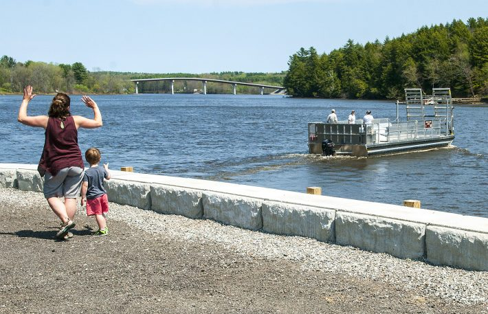 Liz Dunn, left, and her son Spencer, 3, of Lyman, wave to the staffers on the Swan Island Ferry from the recently rebuilt parking lot Wednesday on the shore of Kennebec River in Richmond. They'd just returned from a visit to the island.