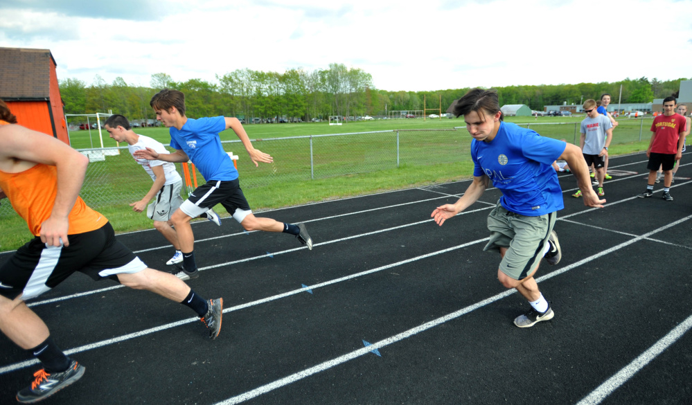 Winslow High School track athletes Jake Warn, left center, and Spencer Miranda sprint on the school's track Wednesday.