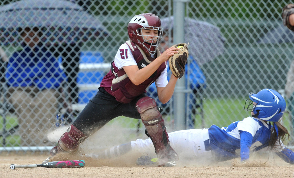 Monmouth Academy catcher Abby Ferland (21) gets the force out at home as Madison Area Memorial High School's Emily Edgerly (8) slides in too late in Madison on Thursday.