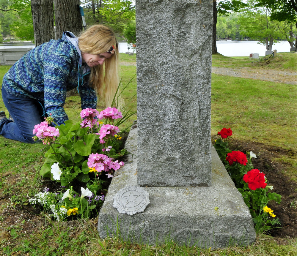 Sara Rushton plants flowers Thursday on both sides of the grave of her grandmother at the Lakeview Cemetery in Oakland for Memorial Day.