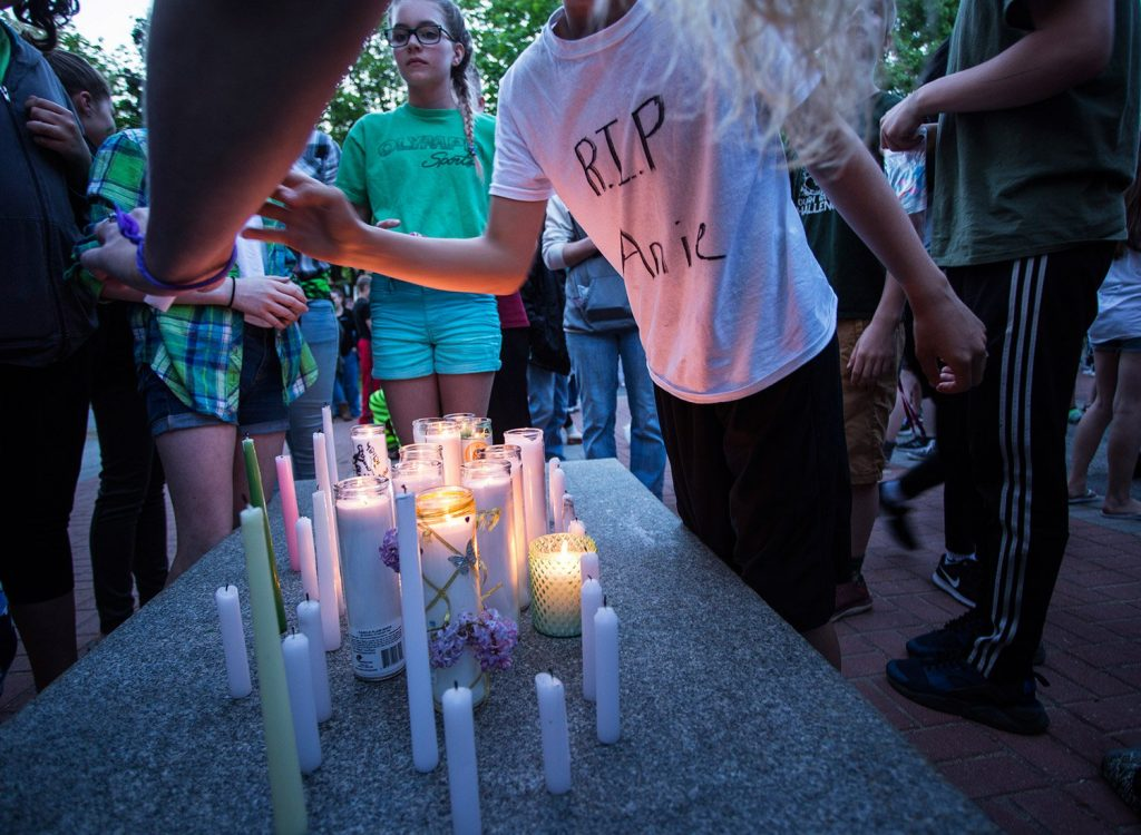 Students combine candles they lit during Wednesday night's vigil for Anie Graham.