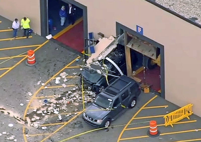 This image from video provided by NBC Boston shows the crash scene Wednesday after a vehicle suddenly accelerated at an auto auction and struck several people before it going through a wall of the building in Billerica, Mass.