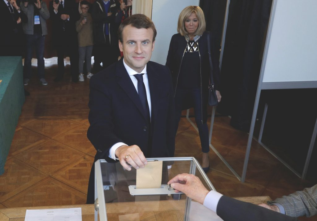 Emmanuel Macron casts his ballot at a polling station while his wife, Brigitte, looks on during the the second round of the 2017 French presidential election on Sunday.