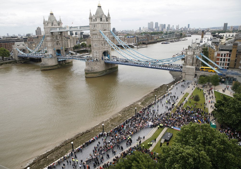 People attend a vigil for victims of Saturday's attack on London Bridge, at Potter's Field Park with Tower Bridge in the background in London, on Monday.
