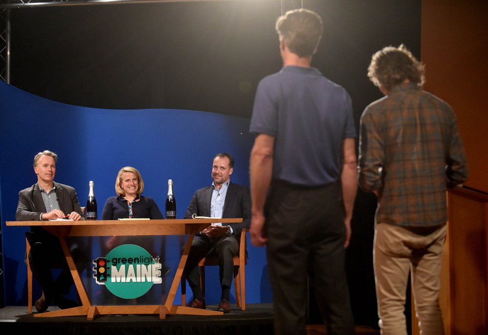 """Greenlight Maine"" judges, from left, Michael Burgmaie of Whipstitch, Betsy Peters, chief revenue officer at Better Lessons, and Michael Petit of JMH Capital listen to a business pitch Tuesday from Bluet sparkling blueberry wine owners Eric Martin, far right, and Michael Terrien, second from left in foreground, during the recording of ""Greenlight Maine"" at Thomas College in Waterville."