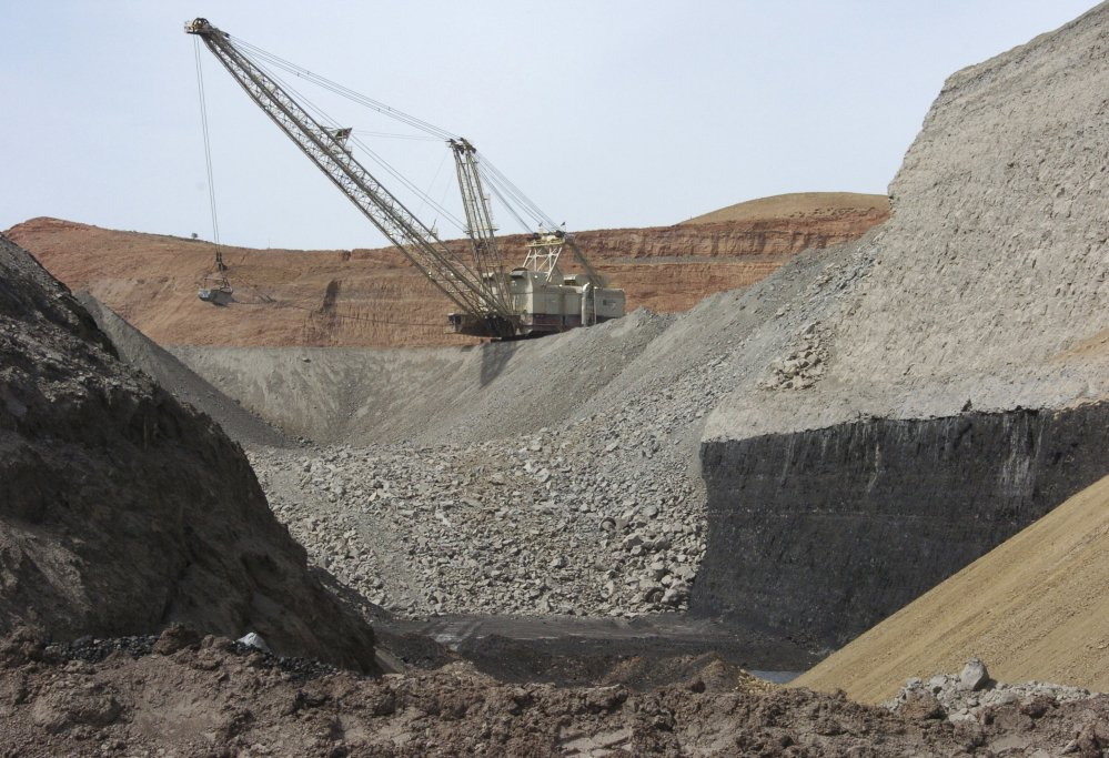 An excavator moves rocks above a coal seam at the Spring Creek Mine in Decker, Mont., in 2013. President Trump has ordered a review of the Clean Power Plan, which targets emissions from coal power plants, and lifted a moratorium on sales of coal mining leases on federal lands.