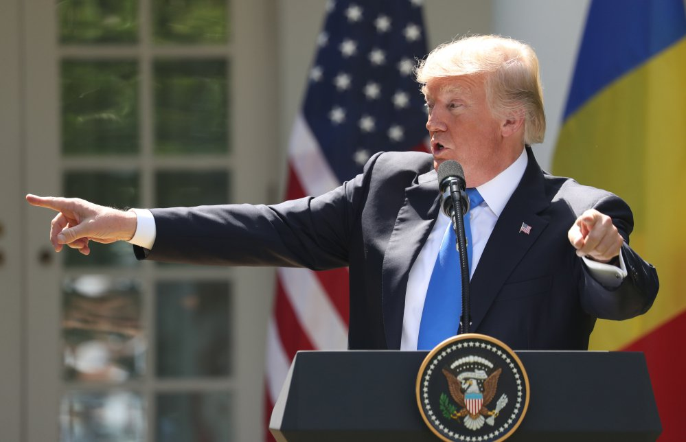 President Trump, accompanied by Romanian President Klaus Werner Iohannis, speaks at a news conference in the Rose Garden at the White House on Friday.