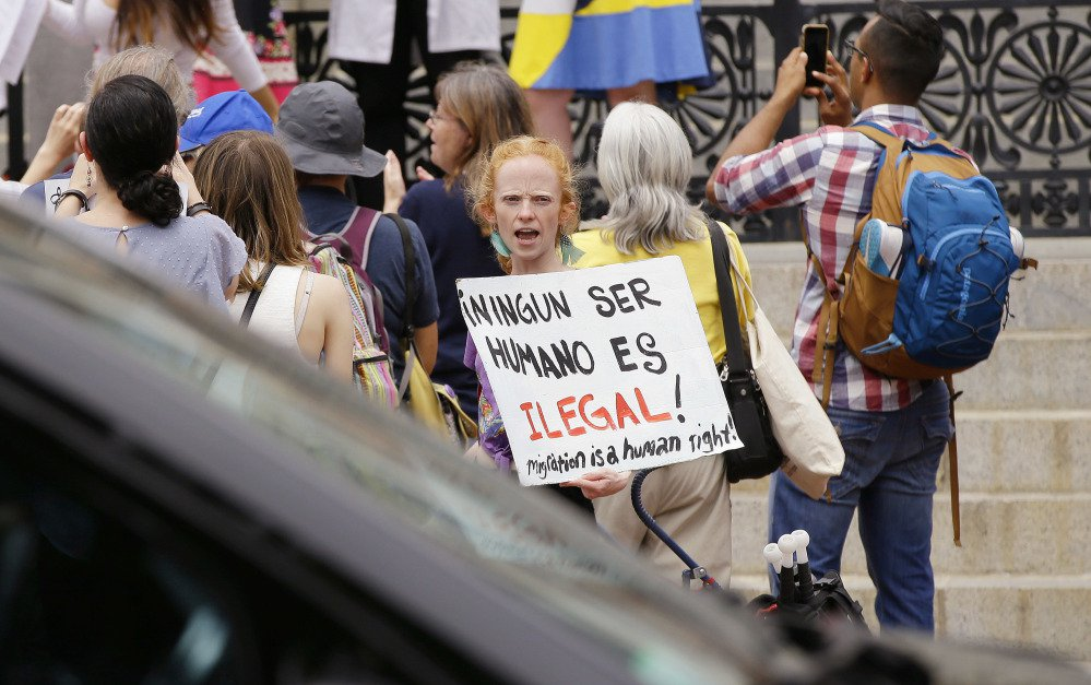 """Associated Press/Stephan Savoia Bostonian Anna Hadingham's sign translates as """"No Human Is Illegal"""" during a Sanctuary State Rally outside the Massachusetts Statehouse Friday in Boston. Inside the building, a sanctuary bill was discussed."""