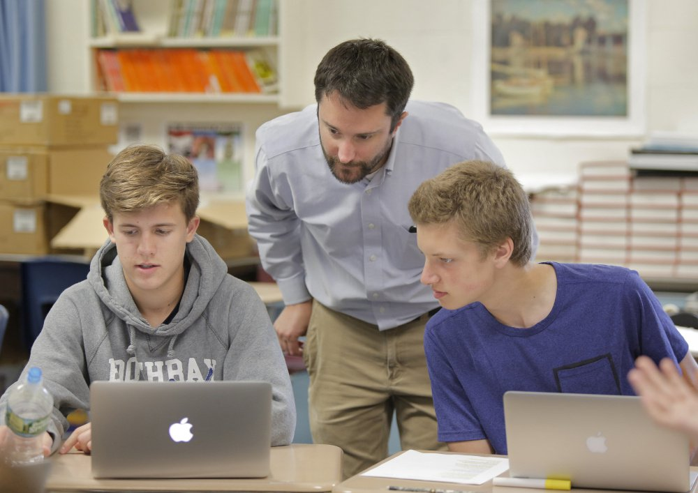 Teacher William Putnam talks with students Hunter Brown, left, and Benjamin Ingalls in a ninth-grade honors English class at Gray-New Gloucester High School. Putnam has adopted the philosophy behind proficiency-based education and practices it in his classes.