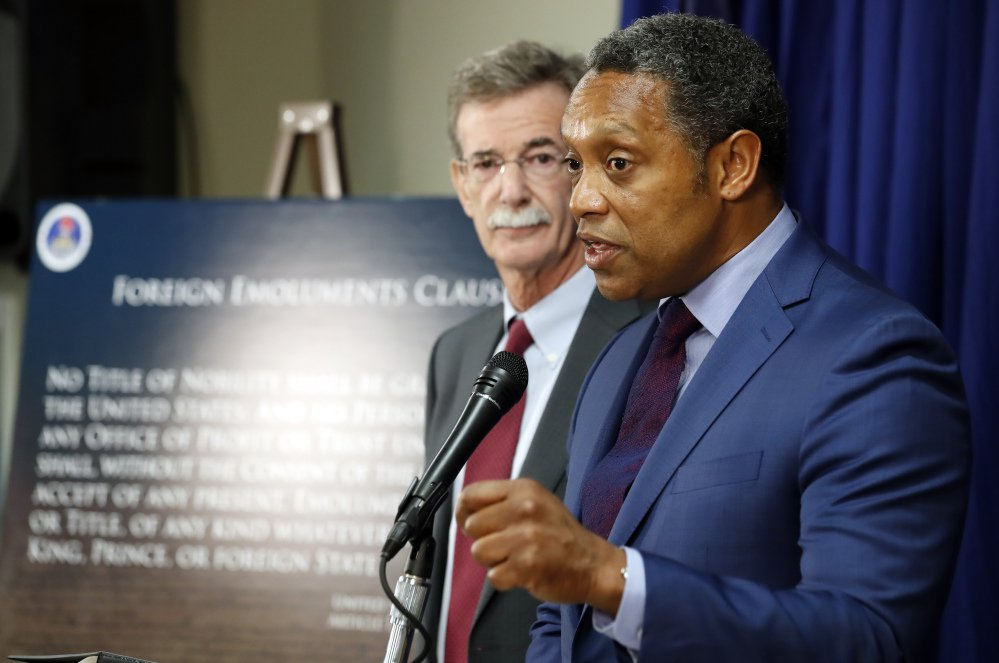 "Maryland Attorney General Brian Frosh listens at left as District of Columbia Attorney General Karl Racine answers a question during a news conference in Washington Monday to announce what they call a ""major lawsuit"" against President Trump. The lawsuit cites Trump's leases, properties and other business ""entanglements"" around the world as the reason for the suit, saying those posed a conflict of interest under a clause of the Constitution."