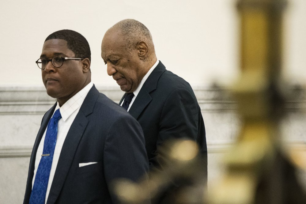 Bill Cosby, accompanied by Andrew Wyatt, walks to the courtroom during jury deliberations in his sexual assault trial at the Montgomery County Courthouse in Norristown, Pa., on Tuesday.