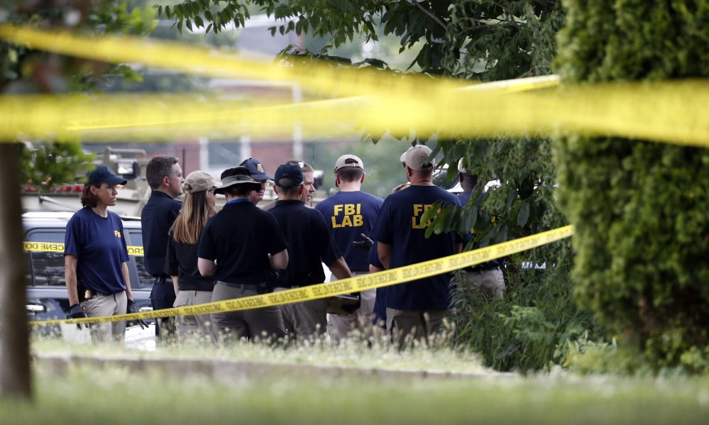 Investigators confer before looking for evidence around the baseball field in Alexandria, Va., on Wednesday, that was the scene of a shooting involving House Majority Whip Steve Scalise of Louisians and others, during congressional baseball practice.