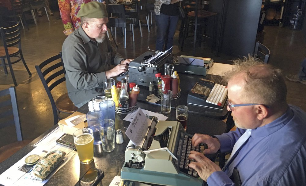 "Joe Van Cleave, left, and Rich Boucher try out vintage typewriters at a ""type-in"" in Albuquerque, N.M., on April 23. ""Type-ins"" are social gatherings in public places where typewriter fans test different vintage machines."