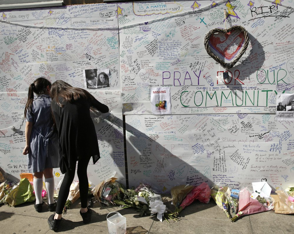 People write messages on a wall for the victims and in support of those affected by the massive fire in the Grenfell Tower in London on Thursday. At least 17 people died.