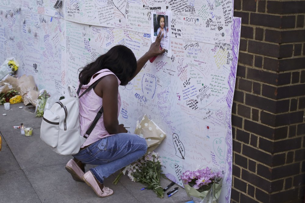 A woman touches a missing poster for 12-year-old Jessica Urbano on a tribute wall after laying flowers on the side of Latymer Community Church next to the fire-gutted Grenfell Tower in London on Friday.