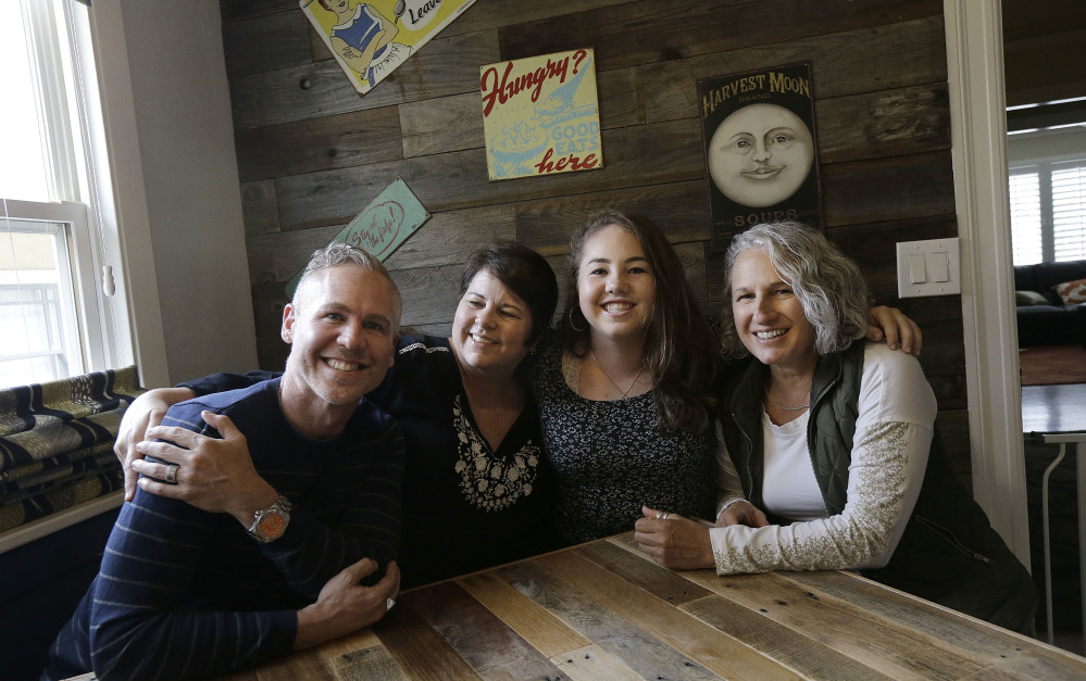 "Madison Bonner-Bianchi, second from right, poses for photos with her parents, from left, Mark Shumway, Kimberli Bonner and Victoria Bianchi in Oakland, Calif. Madison says her relationship with her parents is like anyone else's – ""I just happen to have three of them."""