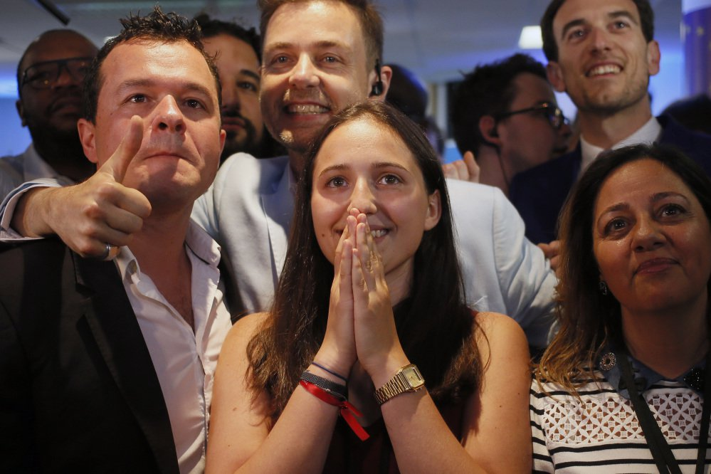 La Republique en Marche party members react after the announcement of the partial official results and polling agencies projections in the final round of parliamentary elections are announced at the party headquarters, in Paris, France, Sunday, June 18, 2017. Partial official results show President Macron's new centrist party with clear lead in parliamentary election.(AP Photo/Francois Mori)