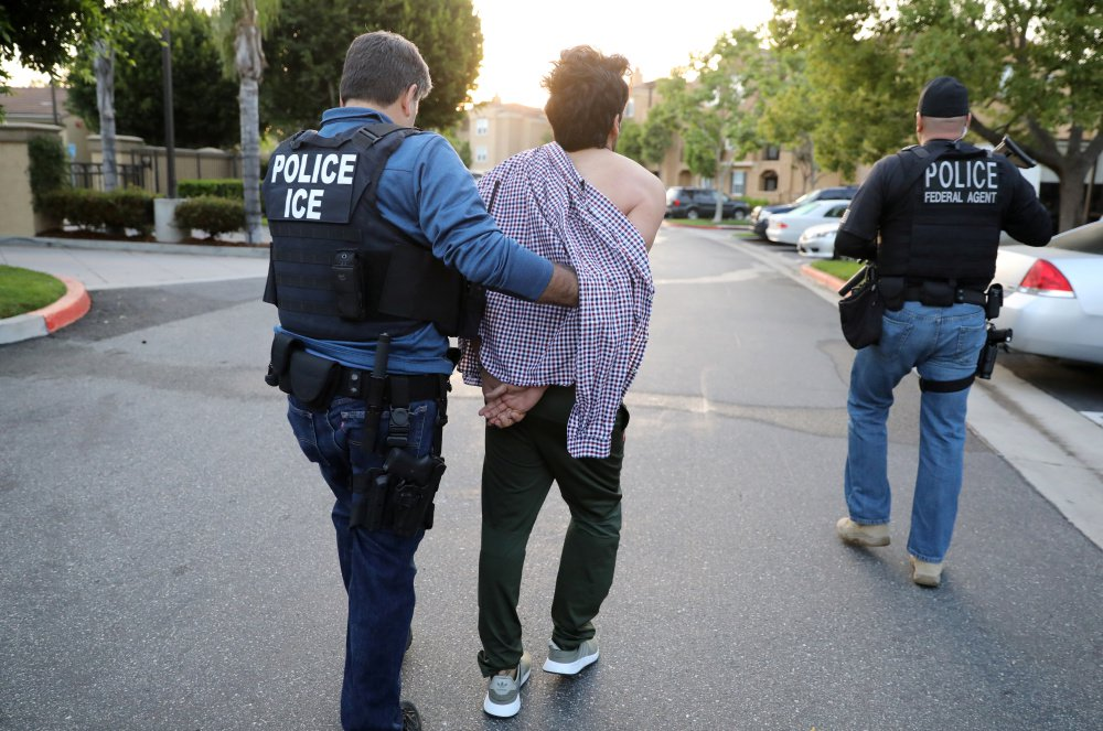 U.S. Immigration and Customs Enforcement agents arrest an Iranian immigrant in San Clemente, Calif., last month. A group of former detainees in Colorado is suing a private detention center company claiming they have been exploited for their labor.