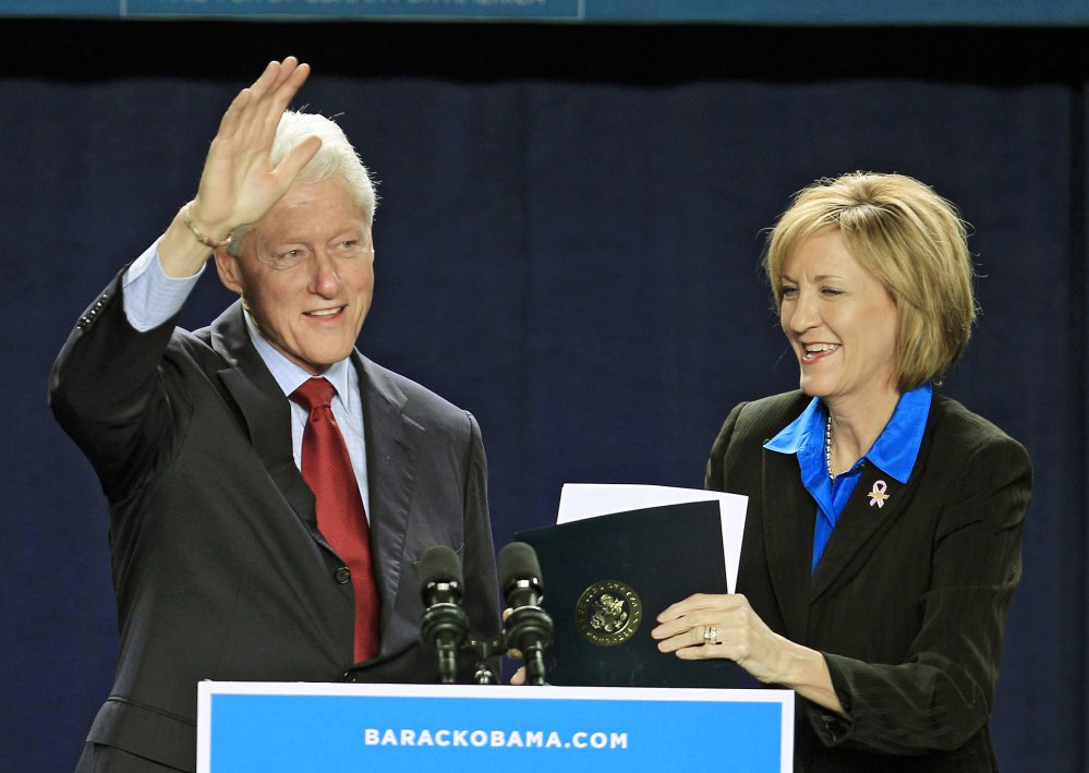 Bill Clinton waves after being introduced by U.S. Rep. Betty Sutton, D-Ohio, right, during a campaign event for President Barack Obama in Parma, Ohio, in 2012.