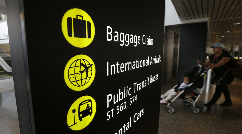 "A woman pushes a stroller near a sign for international arrivals Monday at the Seattle-Tacoma International Airport. The U.S. Supreme Court said Monday that President Trump's travel ban on visitors from Iran, Libya, Somalia, Sudan, Syria and Yemen can be enforced if those visitors lack a ""credible claim of a bona fide relationship with a person or entity in the United States."""